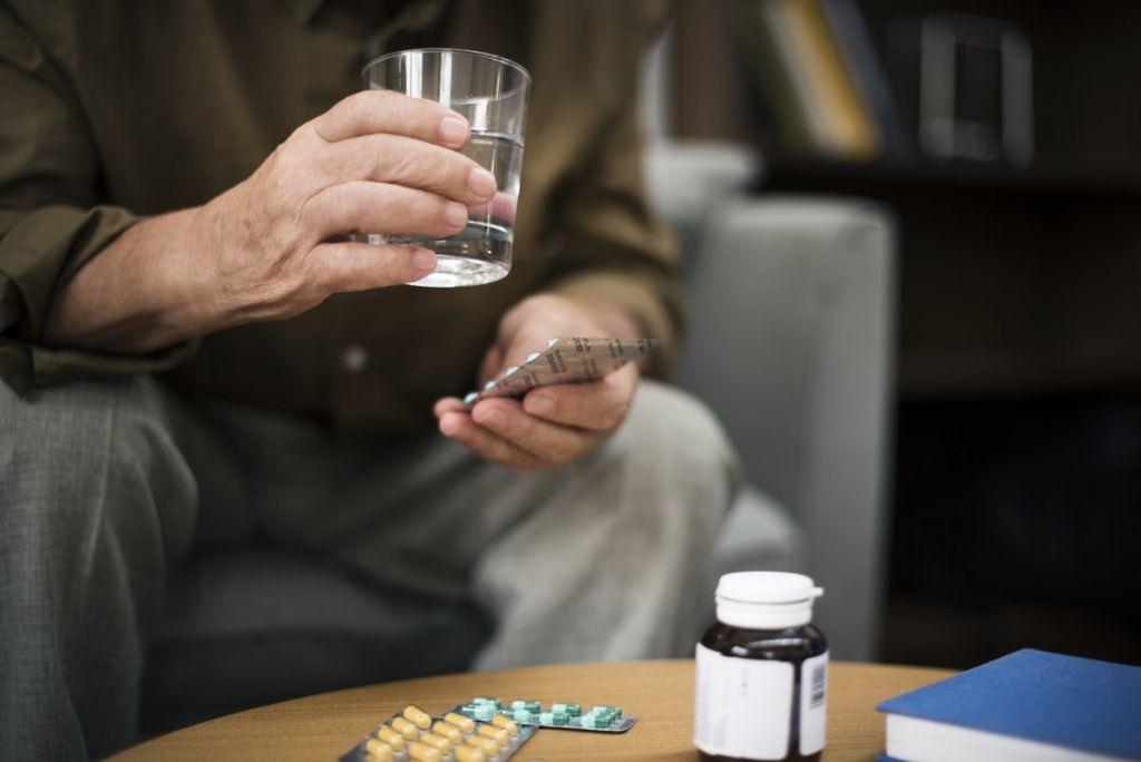 elderly person taking pills / CBD capsules