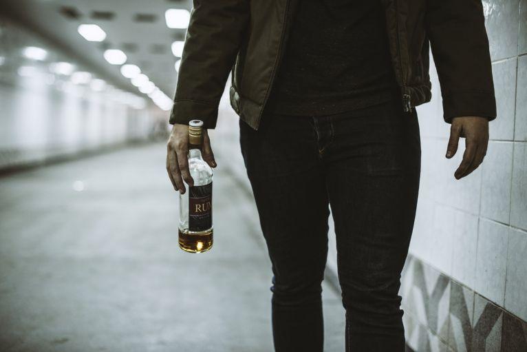 Alcoholic Homeless Holding Liquor Bottle